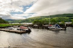 A view of Loch Tay boat station with background highland hills in cloudy weather Royalty Free Stock Photo