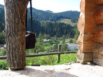 View from log house porch on river and forested mountains. Photo bag hangs on a log Royalty Free Stock Image