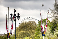 View on the London Eye behind the trees in London, UK Stock Image
