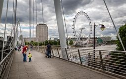 View of the London Eye from Golden Jubilee Bridge in London, UK royalty free stock images