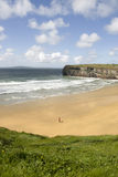 View of lone man at beach and cliffs in Ballybunion Royalty Free Stock Photo