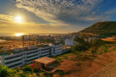 Beach in Agadir city at sunset, Morocco. View of long, wide beach in Agadir city at sunset, Morocco. The hill bears the inscription in Arabic: God, Country, King Royalty Free Stock Photo