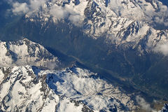 View looking down on Snow capped mountains from airplane seat Stock Images