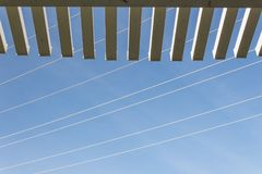 View looking up through the edge of a pergola at blue sky with power lines. Copy space, horizontal aspect Royalty Free Stock Images