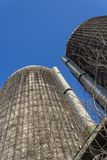 View looking up the face of two old concrete silos against a blue sky stock photos