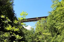 Railroad bridge across the gorge at Watkins Glen State Park. View looking up from the gorge trail on a sunny day. Bright blue sky in the background stock photo