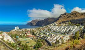 View of the Los Gigantes port and volcanic cliffs on the west coast of the Tenerife island. Sunny day, clear blue sky with little royalty free stock photography