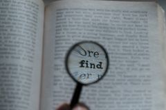View through loupe at book. Word - find Stock Photo