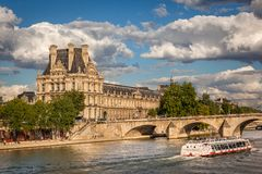View of the Louvre Museum and Pont Royal, Paris. View of the Louvre Museum and a Bateau Mouche crossing Pont Royal Stock Image
