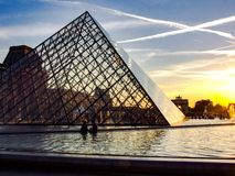 Louvre and glass piramid during sunset. View on Louvre piramid entry in sunset light. Photo tken in 2009. Contrails crossing on the sky. Arc de Triomphe in the Stock Photo