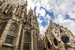 View from low angle on Sagrada Familia. View from low angle on side of Sagrada Familia with blue sky and white clouds Stock Image
