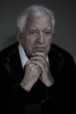 View of low-spirited man. Vertical view of low-spirited older man sitting alone Stock Images