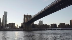 A view of Lower Manhattan skyline filmed from the boat in the East River under the Brooklyn Bridge in New York, United stock footage