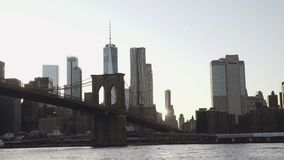 A view of Lower Manhattan skyline with One World Trade Center filmed from the boat in the East River under the Brooklyn stock video footage