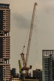 View of luffing jib tower crane at condominium construction site Royalty Free Stock Photo
