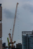 View of luffing jib tower crane at condominium construction site Stock Photo