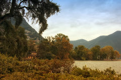 View on Lugano lake. In foreground are trees and bushes. In the middle can be seen lake and pretty haus. Mountains and sky in back plane Stock Images