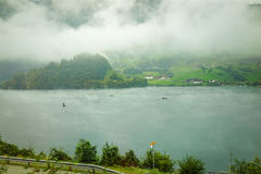 View of Lungern lake with boats and morning fog and mist in autu. Mn, Switzerland Royalty Free Stock Image