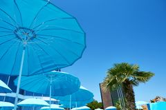 View of a luxury resort hotel with turquoise umbrella against a blue sky. Summer beach vacation concept stock photos