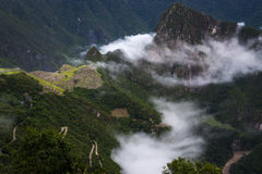 View of Machu Picchu surrounded by clouds from the Sun Gate and the Urubamba River, in Peru Royalty Free Stock Photography