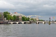 View at Magere Brug, famous Dutch bridge in Amsterdam Canals. Amsterdam, The Netherlands - June 19, 2018: View at Magere Brug, famous bridge in Amsterdam Canals royalty free stock photos