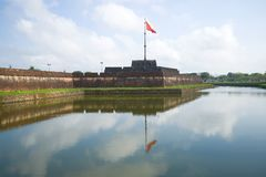 View of the main bastion of the ancient fortress with a waving national flag. Hue, Vietnam royalty free stock images