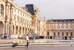 View of main courtyard of Louvre Museum with pyramid. Royalty Free Stock Image