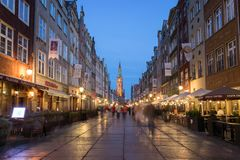 Long Lane in Gdansk at dusk. View of the Main Town Hall and tourists and local people strolling on the Long Lane at the Main Town Old Town in Gdansk, Poland, in Royalty Free Stock Photo