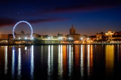 View of Malaga city and Ferris wheel from harbour, Malaga, Spain. Long exposure royalty free stock photography