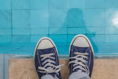 View of male feet at swimming pool side. Stock Photos
