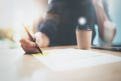 View of male hand making notes on paper document while sitting at the wooden table at sunny office.Blurred background Stock Photo