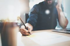 View of male hand making notes on paper document while sitting at the wooden table at sunny office.Blurred background Stock Photos