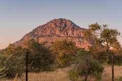 A view of the male hill at Tsodilo Hills, glowing pink during sunset. Tsodillo hills is a UNESCO world heritage site featuring. Ancient San rock paintings stock images