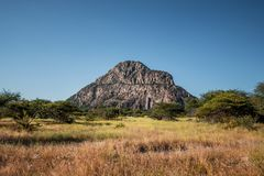 A view of the male hill at Tsodilo Hills, a UNESCO world heritage site featuring ancient San rock paintings. Pictured amid grassy. And arid plains royalty free stock image