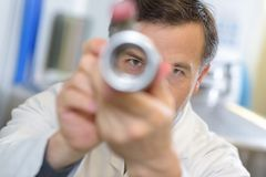 View male scientist through metal tube Royalty Free Stock Photos