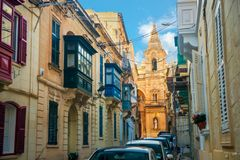View of maltese narrow streets with balconies and cathedral in S. Liema city in day, Malta Royalty Free Stock Photo