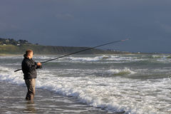 View of man fishing from beach at Harlech, Wales Stock Photo
