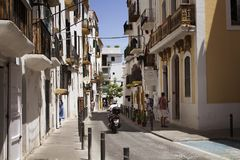 View of a man riding motorcycle. And people on one of narrow, historical streets in Ibiza old town. Image reflects culture and lifestyle of the island Stock Photos