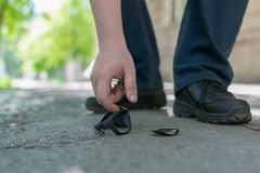 View of the feet of a man and broken sunglasses. View of a man`s feet on a city street that stands on an asphalt pedestrian road and raises fallen and broken stock images