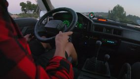 Traveling in small japanese van in mountains. View of man in shorts behind wheel of camping van or big truck, changing gears and turning to new lane. Vintage stock footage