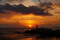 View of a man silhouette standing on sea stone beach and shooting selfie with beautiful amazing sunset of orange red colors. Beaut royalty free stock images