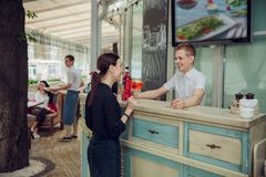 View of man standing at bar counter and making cocktail for woman staying near. royalty free stock photos