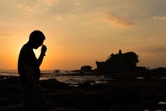 A man take of glasses in silhouette look at Pura Tanah lot, Bali, Indonesia. View of a man take of glasses in silhouette look at Pura Tanah lot, Bali, Indonesia stock photos