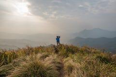 A man take a photo at the top of Phu Chi Fa in Chiang Rai, Thail. View of a man take a photo at the top of Phu Chi Fa in Chiang Rai, Thailand stock photography
