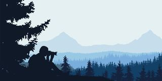 View of a man taking a forest with a mountain landscape with woo. Ds in the background under a blue-gray cloudy sky Royalty Free Stock Photos