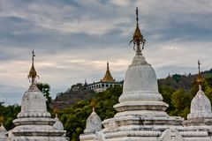 A view on Mandalay Hill from Kuthodaw Pagoda, Mandalay, Myanmar. Kuthodaw Pagoda is a Buddhist stupa, located in Mandalay, Burma, that contains the world`s stock photo