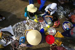 View of market stalls and a woman pavement vendor selling fish Royalty Free Stock Photo