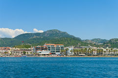 View of marmaris resorts and beach from sea. View of marmaris hotels and beach with sunbeds and umbrellas from sea on sunny day with clear blue sky and green Royalty Free Stock Image
