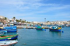 View of Marsaxlokk town and harbour, Malta. Traditional Maltese Dghajsa fishing boats in the harbour with waterfront buildings to the rear, Marsaxlokk, Malta Royalty Free Stock Photography