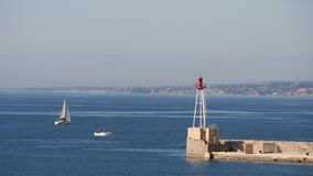 Seascape of Marseille, France. View from Marseille over the Mediterranean Sea. There is a sailboat passing by and a lighthouse at the end of a pier. Filmed in stock video